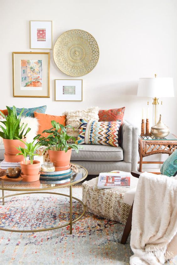 a pretty and airy global style living room with colorful pillows, potted plants, a mini gallery wall with art