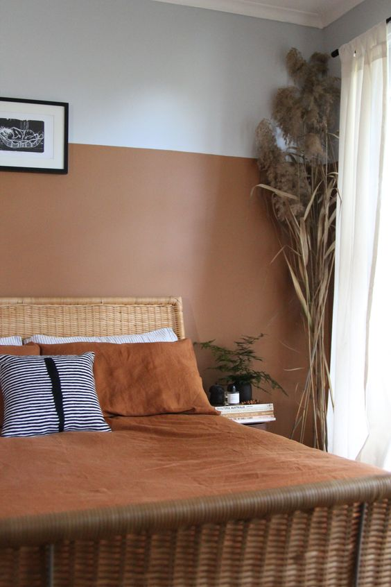 an earthy tone bedroom with a terracotta color block wall, a rattan bed, grasses and potted greenery