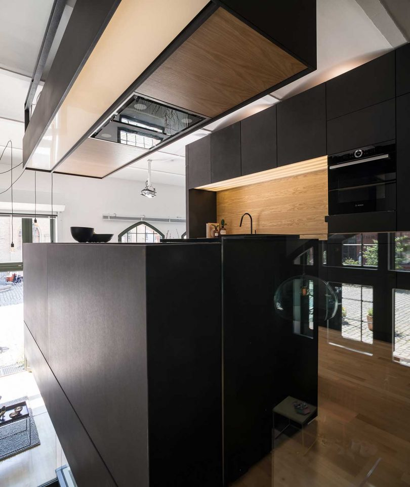 A hood over the island contains built-in lights and storage space, too, and finishes the look of the space