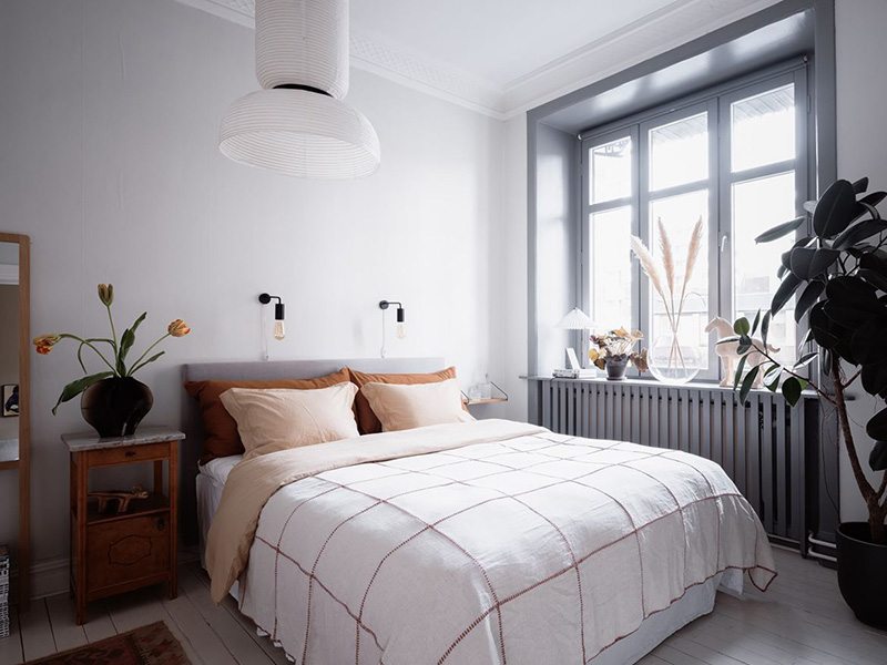 The bedroom is done in mostly white and grey, there's cool and comfy furniture and you may see printed bedding