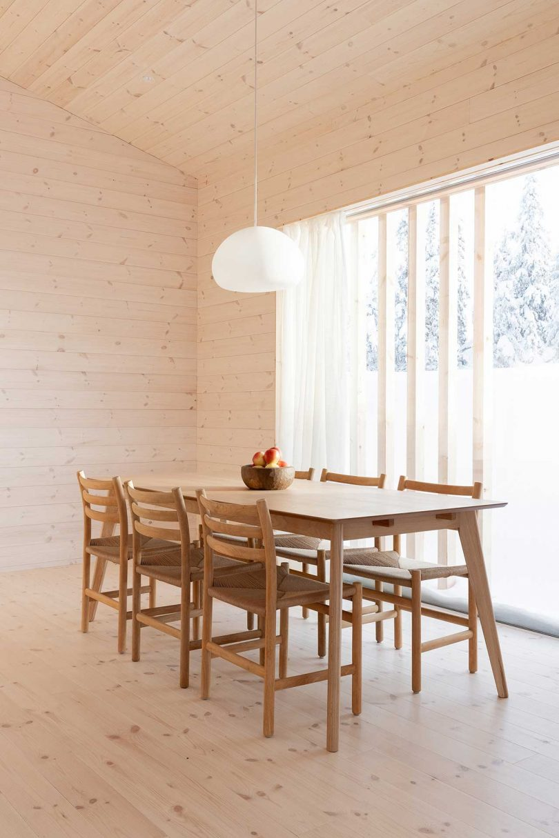 The dining space is very laconic, with a wooden dining set and a pendant lamp - everything here is centered around the views