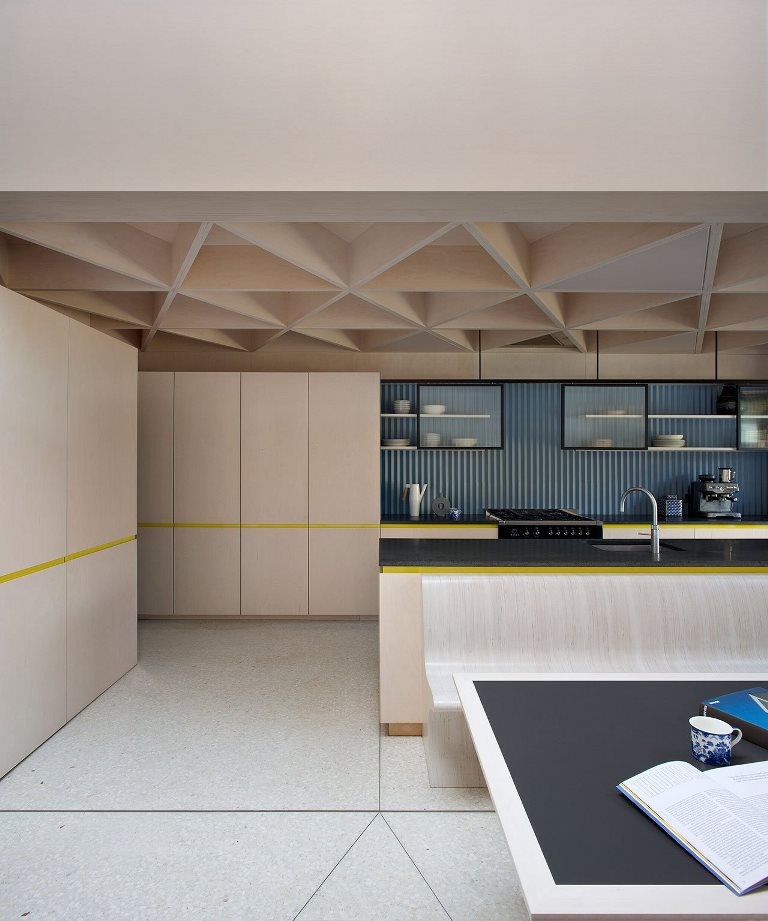 The kitche features a geometric ceiling, a blue corrugated steel backsplash and a black stone countertop