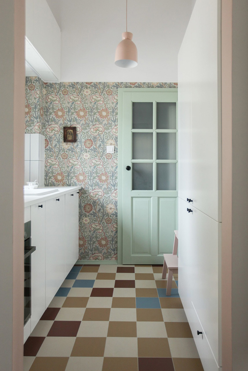 There's a small kitchen with Scandinavian wallpaper and white cabinetry, colorful tiles on the floor