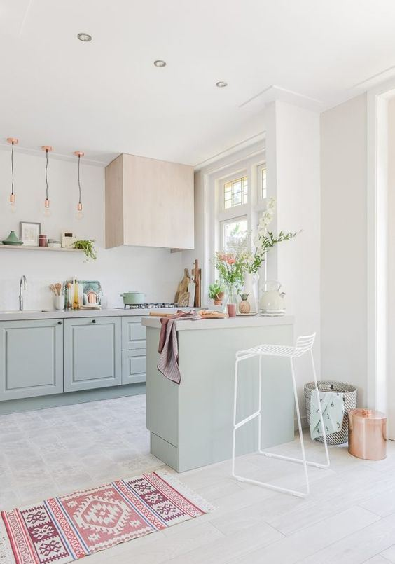 a beautiful pastel kitchen with mint green cabinets, touches of pink, copper and a geometric rug shows off a cool color combo