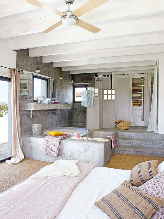 a bedroom combined with a closet and a bathroom clad in concrete, with neutral textiles and printed ones