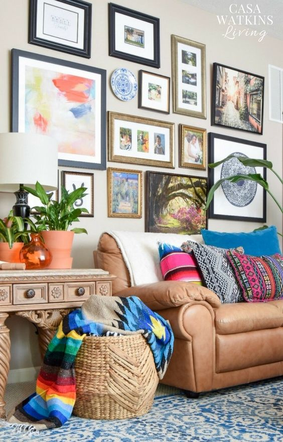 a global eclectic living room with a brown leather sofa, a gallery wall with pretty art, a basket with bold blankets and potted greenery