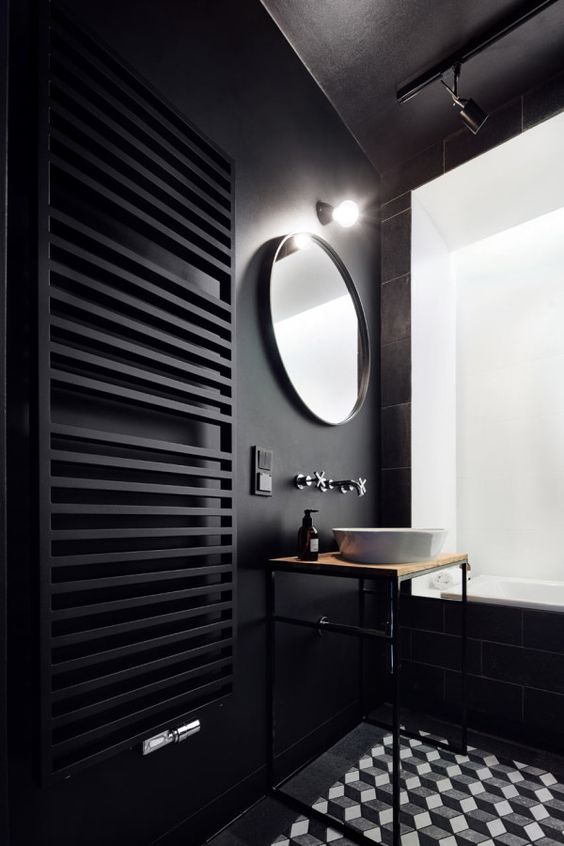 a minimalist black bathroom with matte walls and a radiator, a geometric tile floor and an airy vanity