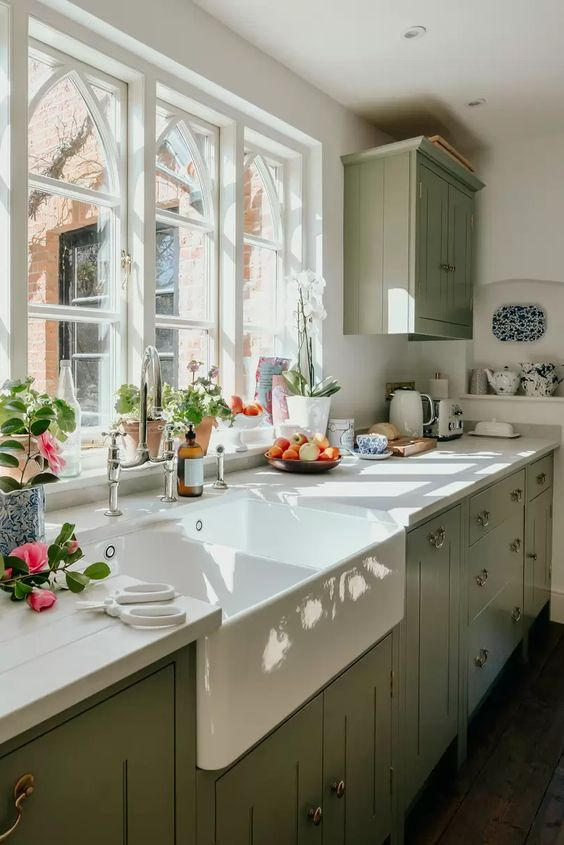 an elegant vintage sage green kitchen with white wooden countertops and a white backsplash, with neutral fixtures is a chic idea
