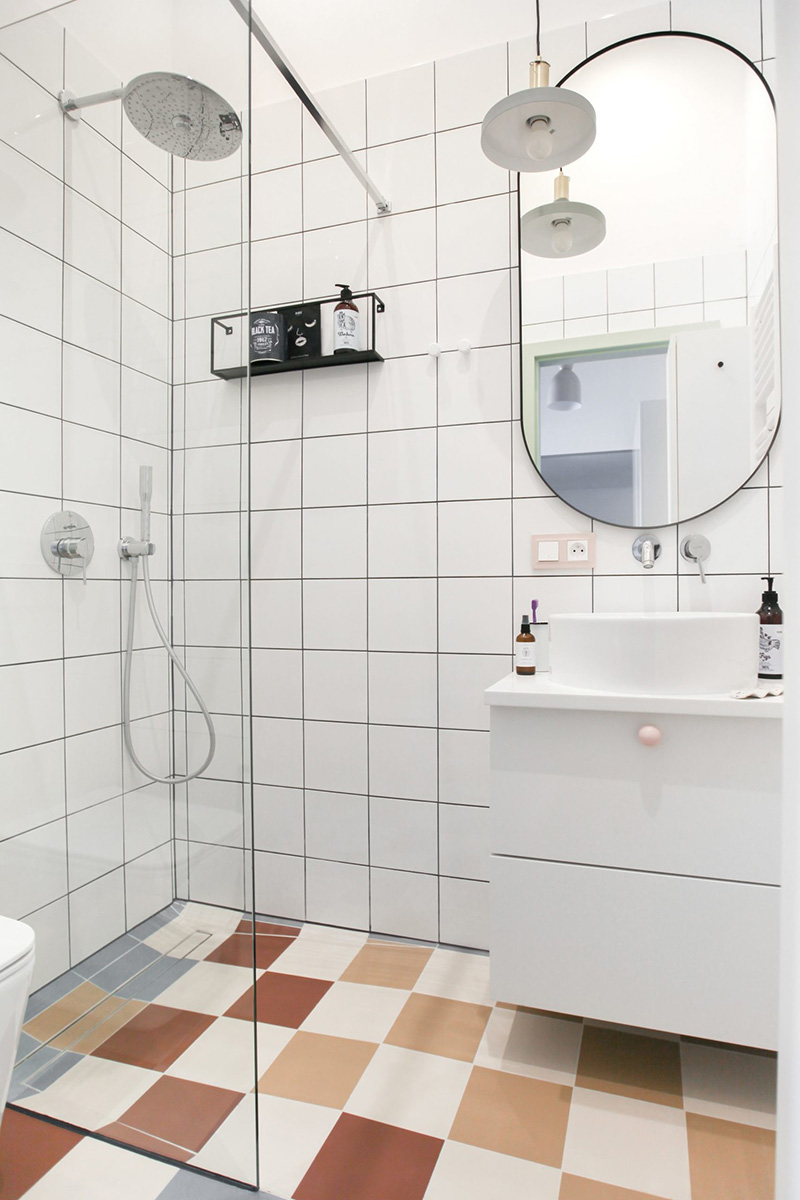 The bathroom is clad with white square tiles and colorful ones on the floor, and there's everything necessary here