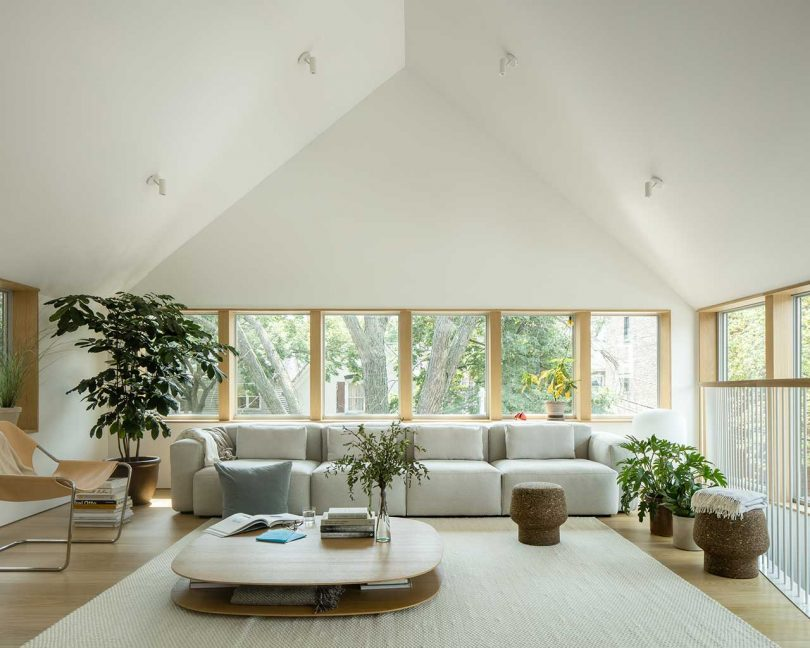 The living room shows off cozy and cool modern furniture, a catchy table and some potted plants
