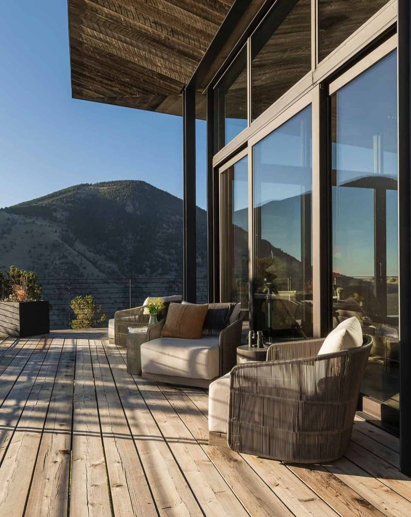 The sun-filled wooden deck is exposed to the rugged landscape around it