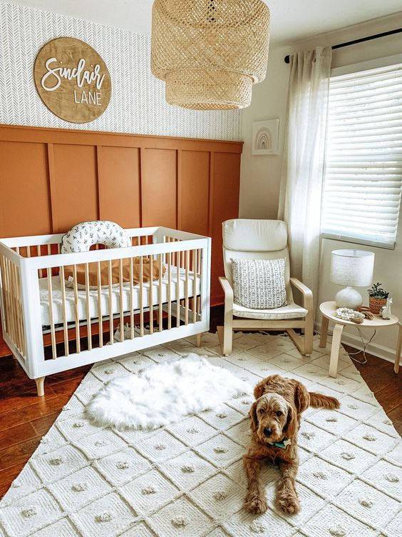 a gender neutral boho nursery with burnt orange paneling, white furniture, a rattan lamp and pretty layered rugs