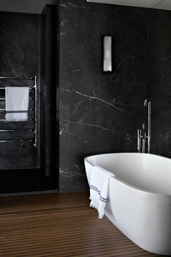 a refined bathroom with black marble walls, a wooden slab floor, a pretty tub and neutral fixtures