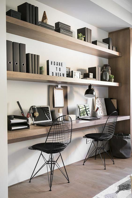 a stylish minimalist home office with floating shelves and a shared desk, metal chairs, table lamps and books