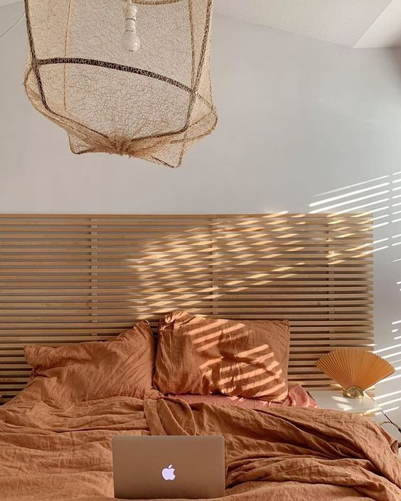 a warm earthy tone bedroom with a light stained bed, a pendant lamp and orange bedding