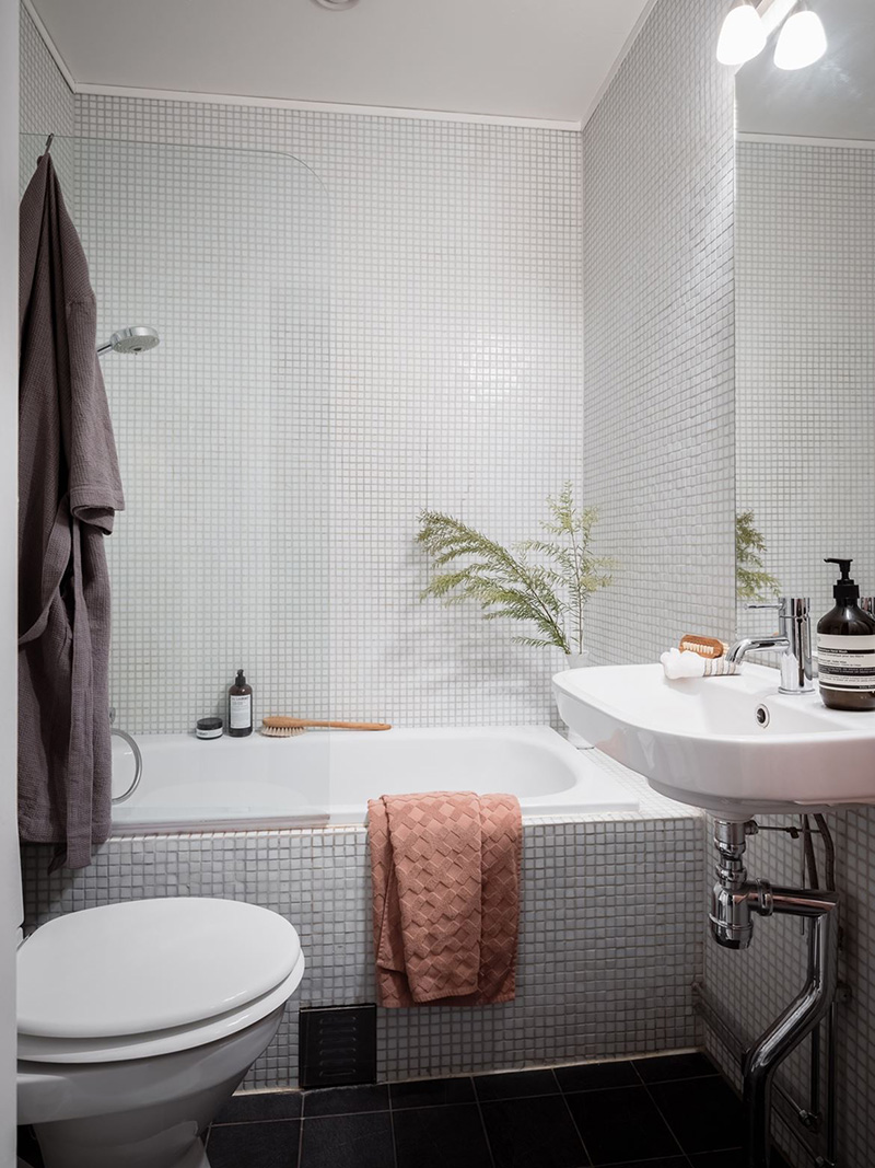 The bathroom is clad with grey textural small scale tiles and white appliances