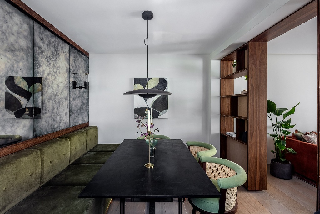 The dining space shows off a banquette seating, a black stone table and some catchy green chairs