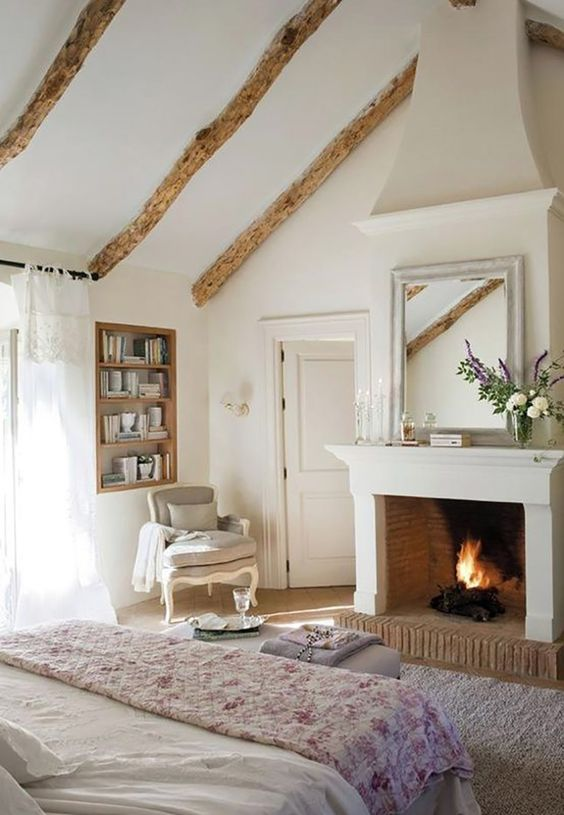 a French chic bedroom with wooden beams, built-in shelves, refined furniture and a working fireplace