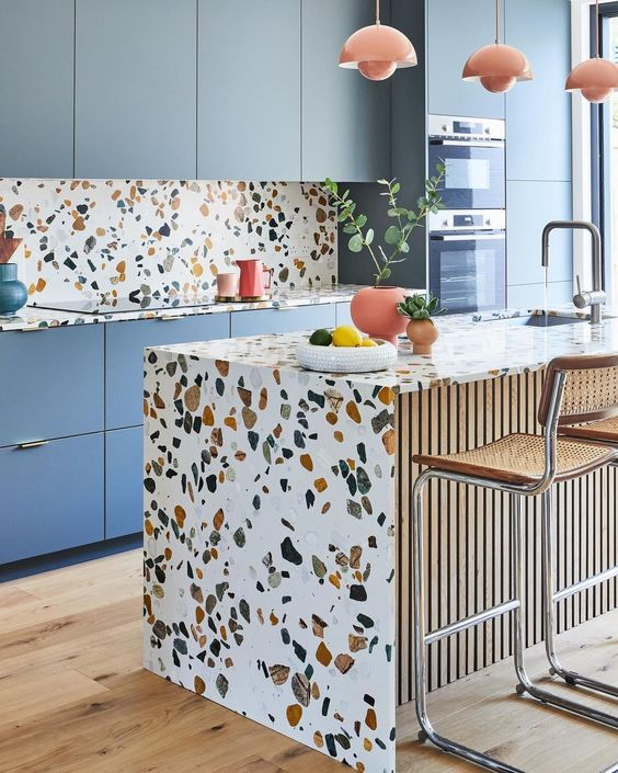 a bright kitchen with blue cabinetry, terrazzo countertops, a backsplash and a kitchen island and coral touches is amazing
