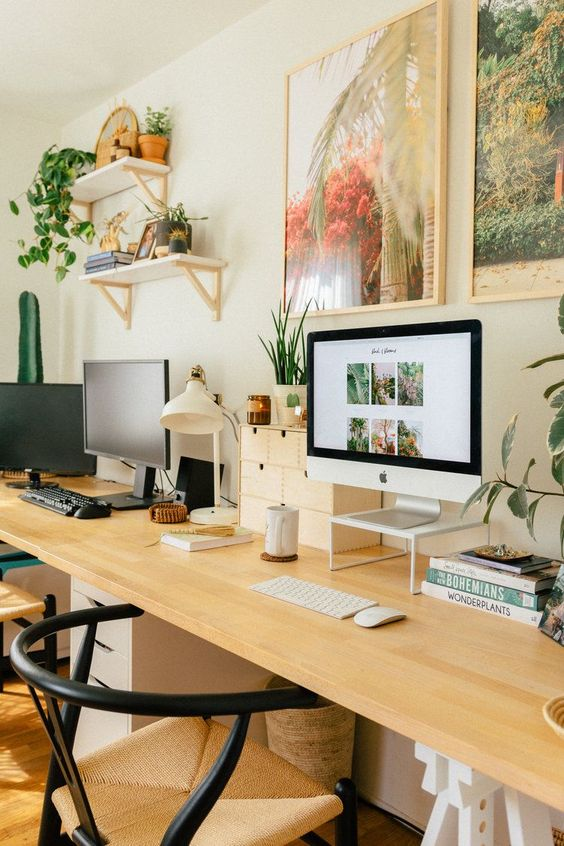 a chic and welcoming home office with a shared desk, woven chairs, bright artworks and potted greenery