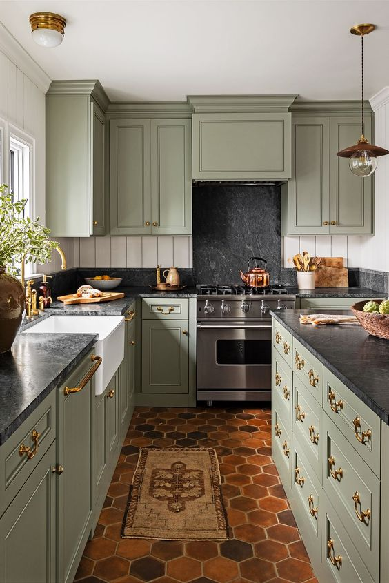 a jaw-dropping sage green vintage kitchen with black stone countertops and a backsplash, with a matching kitchen island and gold handles and fixtures