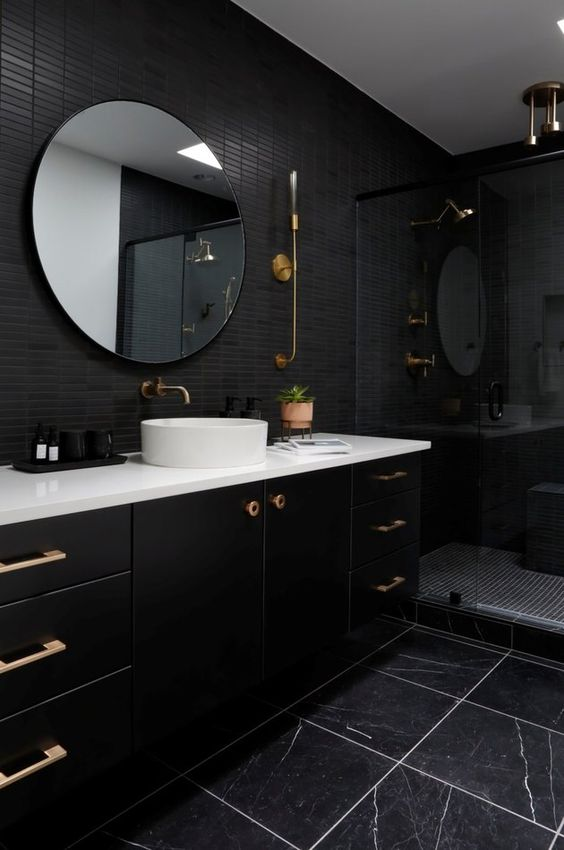 08 a stylish black bathroom with skinny and marble tiles, a large vanity, a round mirror and brass touches