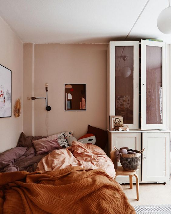 a warm earthy toned bedroom with blush walls, terracotta and blush bedding, wall sconces and a vintage dresser