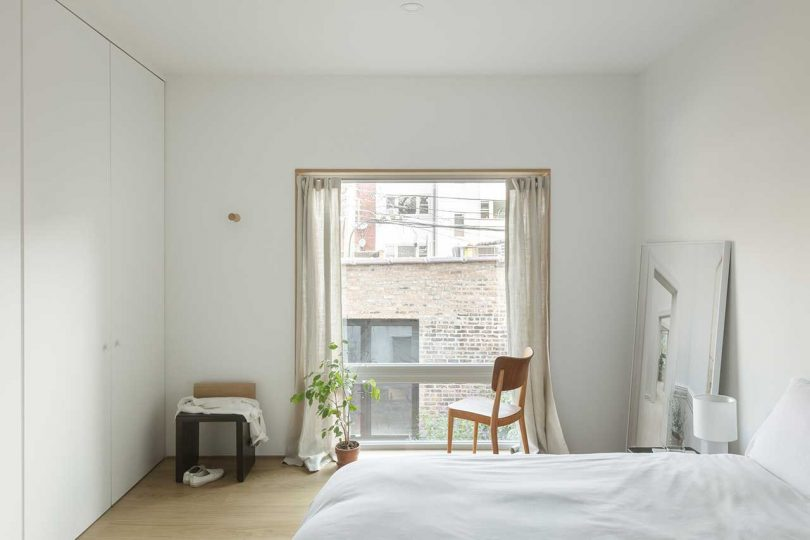 The bedroom is decorated simply, with wardrobes, a bed, some chairs and a single window