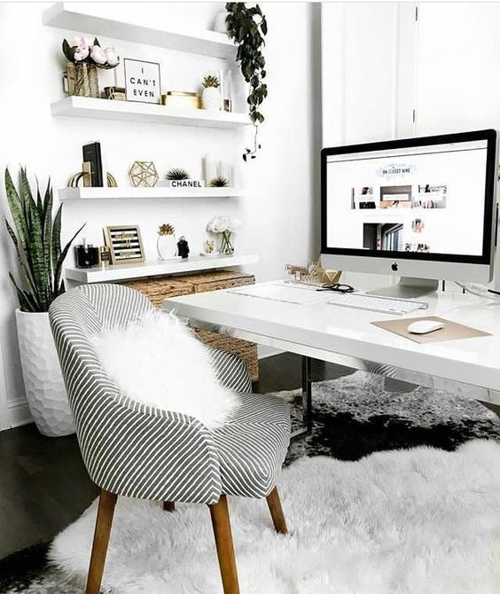 a Scandinavian home office with floating shelves, a desk, a striped chair, some potted plants and baskets