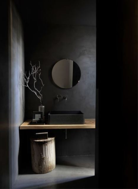 a beautiful minimalist black bathroom with matte walls, a floating vanity, a tree stump and a round mirror