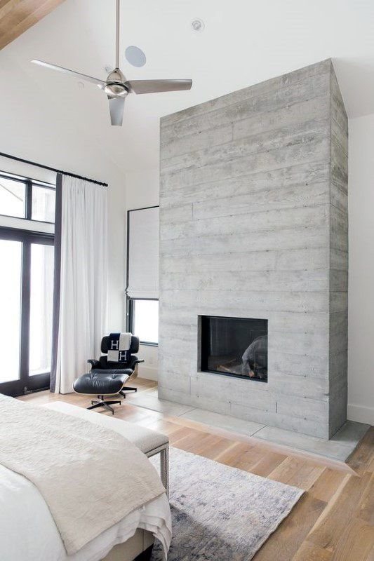 a modern bedroom in neutrals, with much natural light and a concrete fireplace that gives the space a cool look