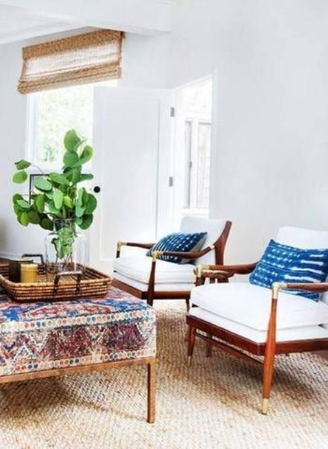 09 a pretty and neutral global style living room with a colorful ottoman, bright pillows and greenery