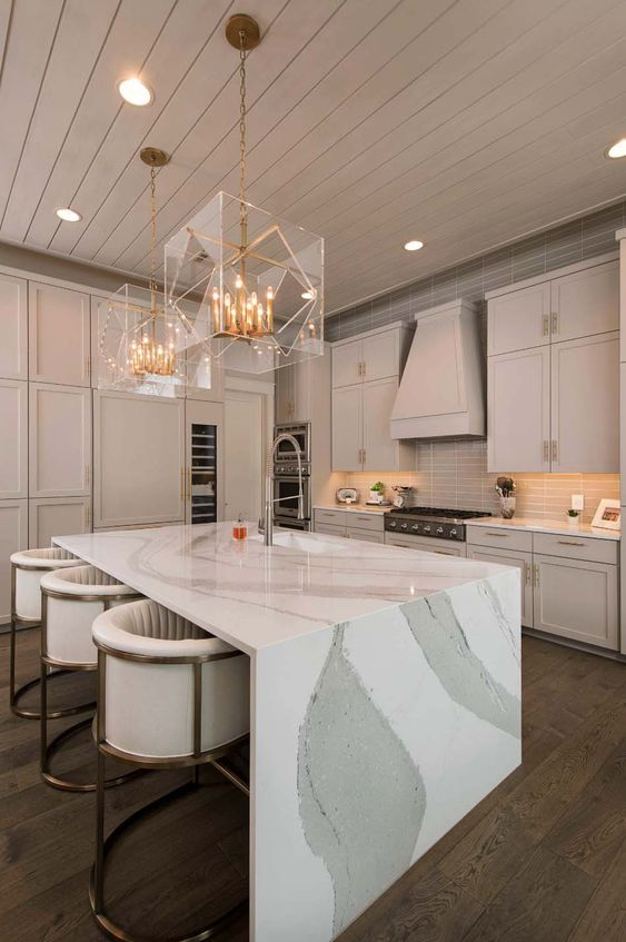 a refined neutral colored kitchen with a jaw dropping kitchen island with a waterfall countertop and stunning gold and sheer glass chandeliers