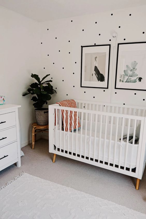 a stylish gender neutral nursery with a polka dot wall, white furniture and a calming gallery wall plus potted plants