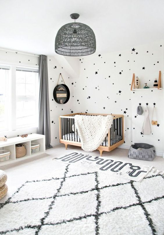 a chic monochromatic nursery in black and white, with a cool modern crib, a shelf and printed textiles