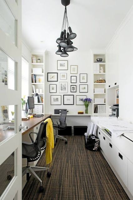 a cool shared Scandinavian home office with a shared desk, chairs, pendant lamps, sleek storage units and a gallery wall