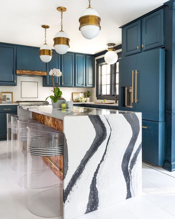 a navy kitchen with brass handles and pendant lamps, a fantastic waterfall kitchen island in black and white and striped stools