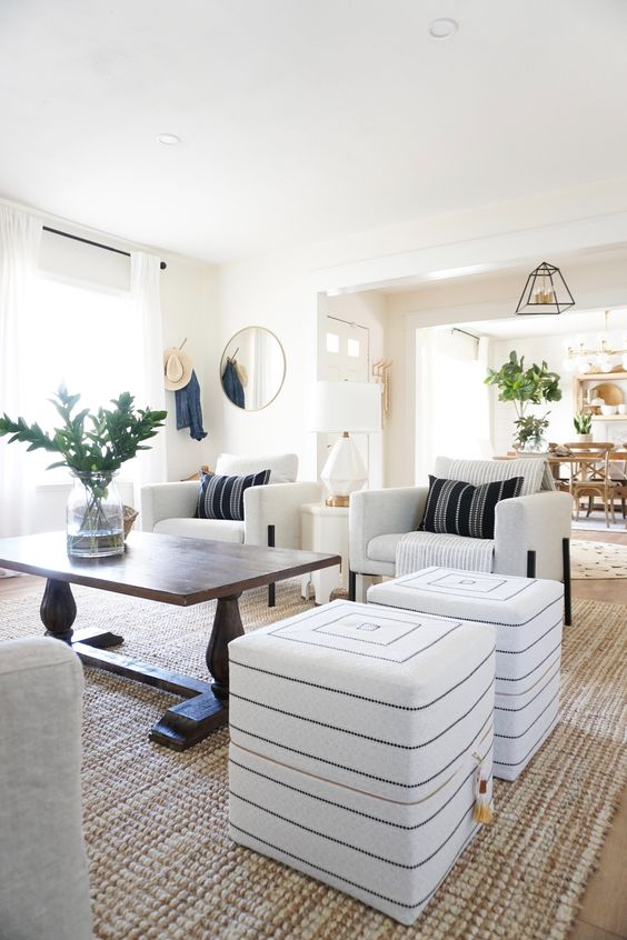 10 a neutral global style living room with pretty Moroccan-inspired ottomans, a wooden table and pretty pillows