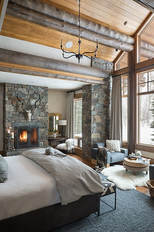 a rustic bedroom with wooden logs on the ceiling, a pillar clad with stone and a stone fireplace
