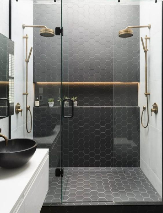 a stylish contemporary bathroom with white square tiles and black hex ones plus brass touches and fixtures
