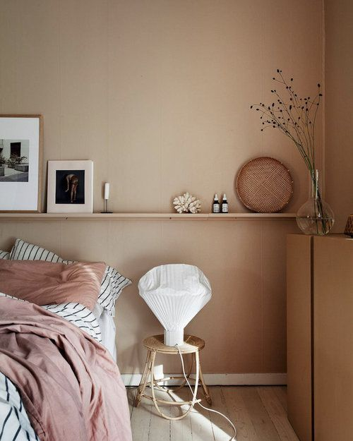 a welcoming and soft earthy toned bedroom with tan walls, pink and striped bedding, artworks and grasses