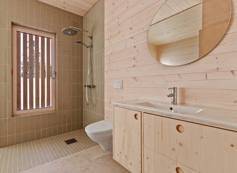 The bathroom is clad with beige tiles and pine wood, it's laconic and simple