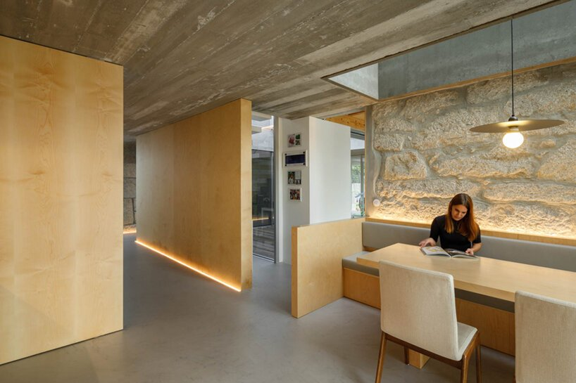 The dining space is all minimal, with built-in benches and a table and a stone lit up wall