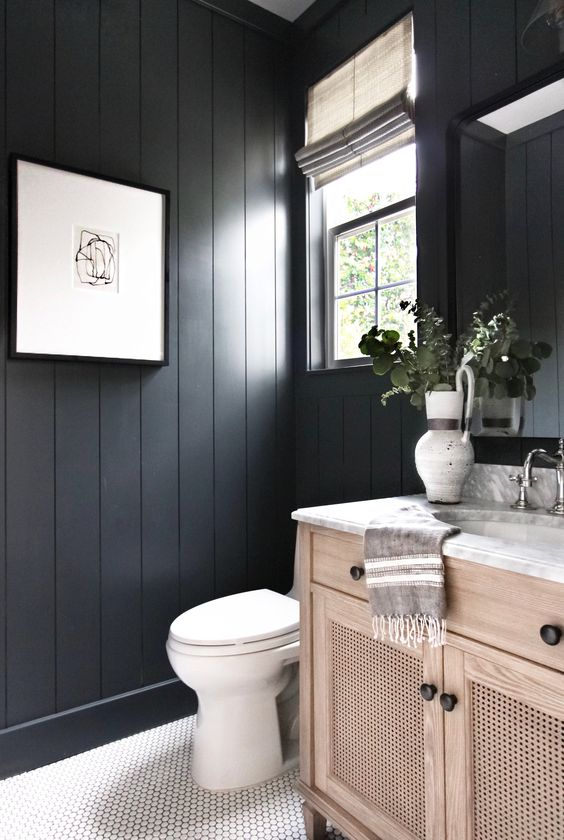 a black bathroom with beadboard walls, a white scale tile floor and a wooden vanity is a very cozy and welcoming space