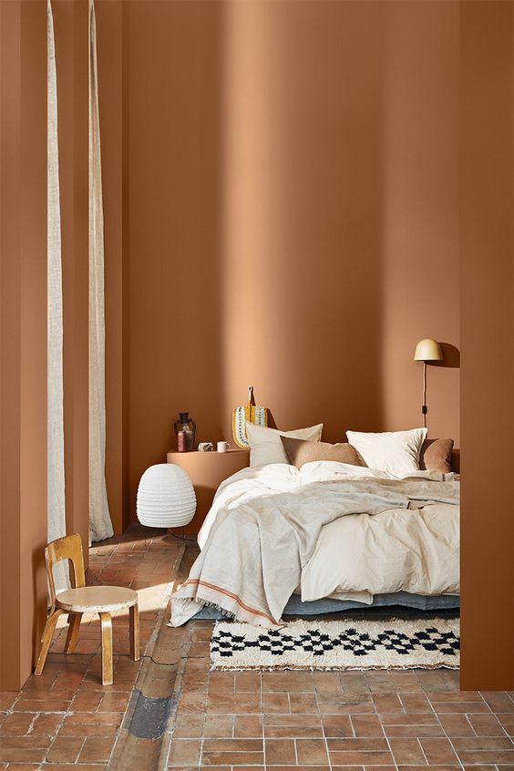 a comforting bedroom with terracotta walls, a brick floor, neutral and terracotta bedding is chic and warm