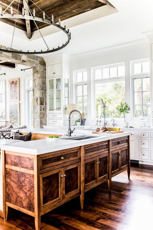 a farmhouse white kitchen with a unique vintage rich stained wooden kitchen island and a large metal chandelier looks wow