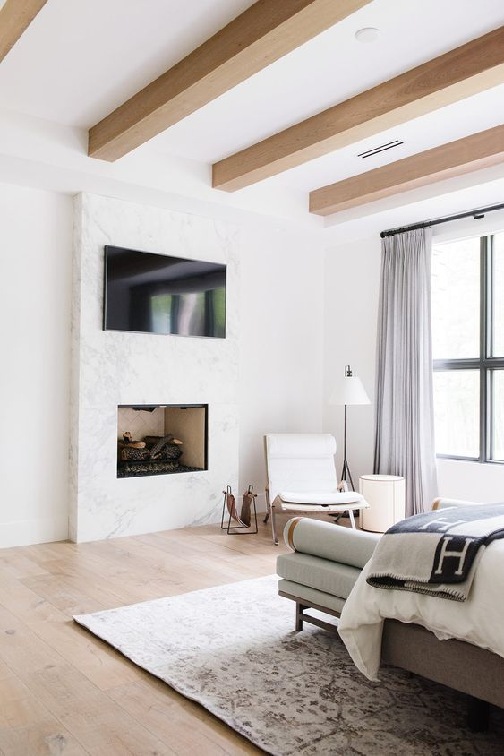 a modern neutral bedroom with sleek wooden beams, stylish furniture, a TV and a working fireplace built in