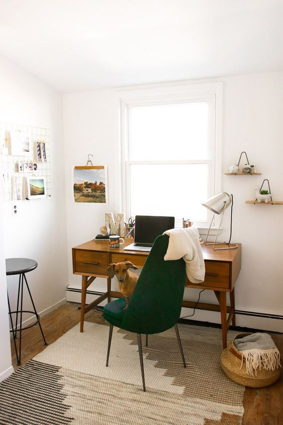 a pretty and cozy mid-century modern home office with a vintage desk, a hunter green chair, a basket, some shelves and a grid