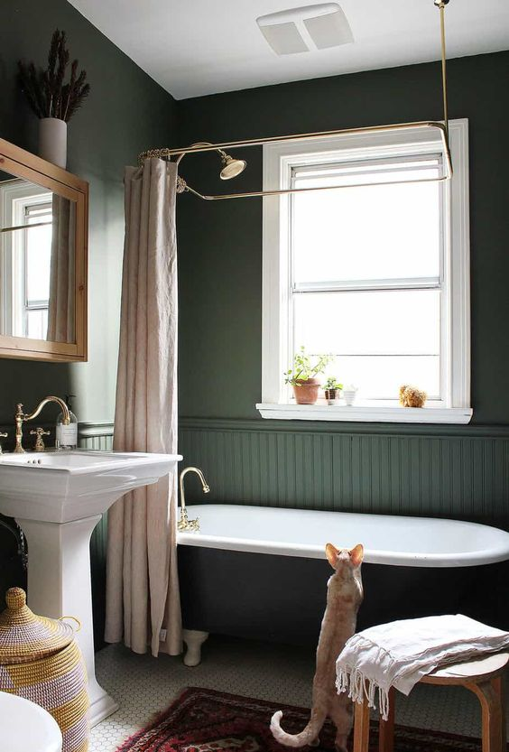a gorgeous dark green bathroom in vintage style, with a clawfoot tub, a free-standing sink and blush textiles