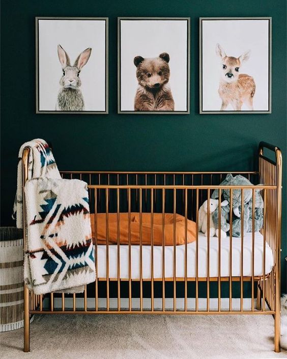 a green nursery with a wildlife gallery wall, a chic brass crib and printed textiles is very cozy